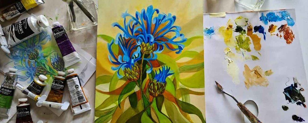 The start of a painting of blue cornflowers with sketch, palette and paints at hand